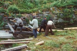 Fra øving i 2001. Bomdragerne drar tømmerstokker opp på vognbanen. Fra venstre: Jon Erik Moen, Trond Grønnæss, Trond Magnum og Erlend Lans Pedersen. Foto: Museumssenteret i Trysil/Engerdal